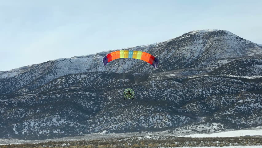 Powered parachute flying low and landing on ice covered lake. Snow covered mountains in winter.  Central Utah winter recreation and sport. Small low power aircraft. - HD stock video clip