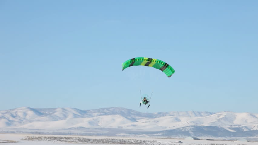 MORONI, UT- CIRCA JAN 2010: Steve Pelton of Moroni flies in Powered parachute circa Jan 2010 in Moroni, Utah, USA. Powered parachute flying across a ice and snow covered lake in winter. - HD stock footage clip