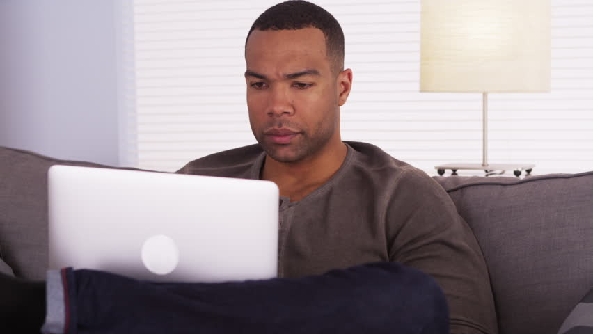 Black man using laptop on couch - HD stock footage clip