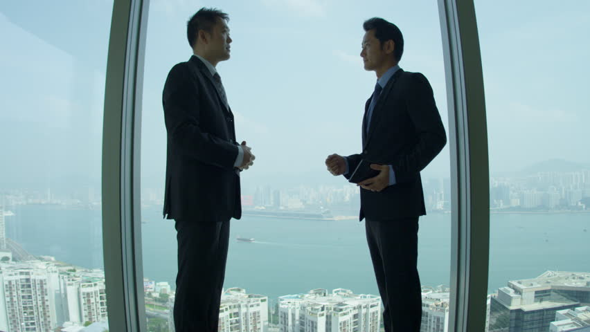 Successful young male Asian Chinese share broker meeting client shaking hands window modern skyscraper building shot on RED EPIC