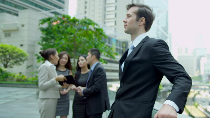 Close up confident male Caucasian business manager foreground successful ethnic business team wireless tablet outdoors downtown shot on RED EPIC   Shutterstock HD Video #6725002