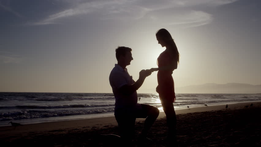 Silhouette Of Man Proposing To Woman On Beach On His Knee