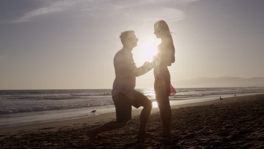 Romantic Silhouette of Man Getting Down on his Knee and Proposing to Woman on Beach - Couple Gets Engaged at Sunset - Man Putting Ring on Girl's Finger | Shutterstock HD Video #6743605