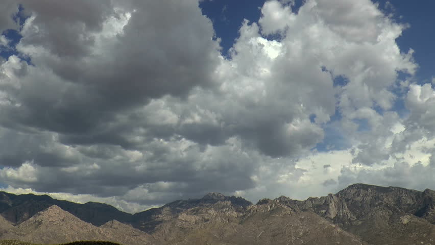 Time Lapse, Thick, dramatic storm cloud mass casts flickering shadows as it sweeps across mountain landscape. 1080p
