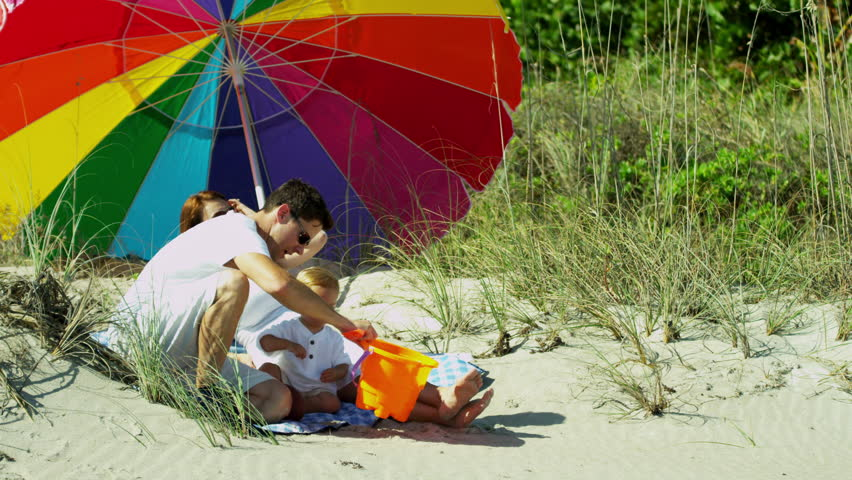 Loving young Caucasian parents dressed in white sitting sun parasol sand beach baby son toy bucket ball vacation travel shot on RED EPIC - 4K stock video clip