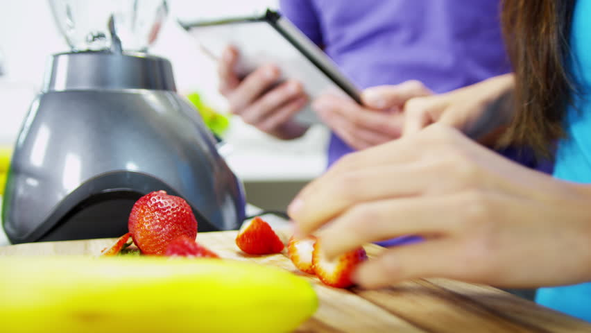 Close up hands no faces young ethnic male female home kitchen counter using wireless tablet recipe prepare fresh healthy organic fruit smoothie drink shot on RED EPIC - 4K stock footage clip