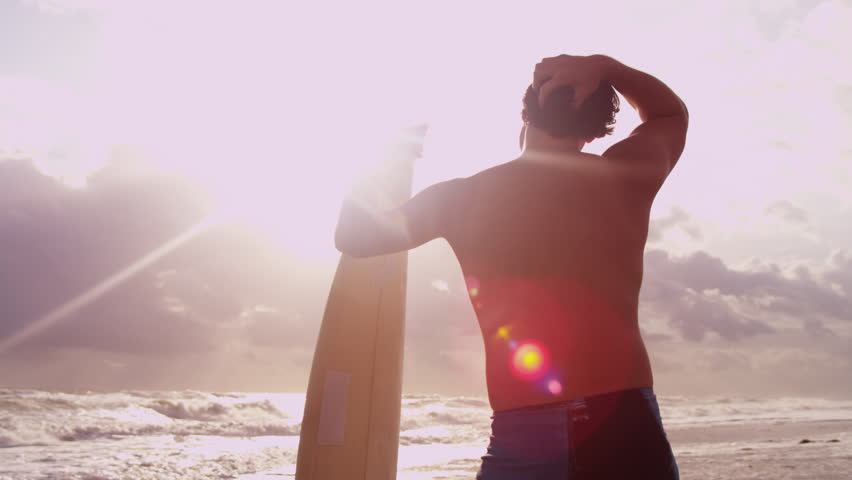 Close up upper body rugged young Asian Chinese male surfer living healthy outdoor lifestyle carrying his board waiting for waves shot on RED EPIC - 4K stock footage clip
