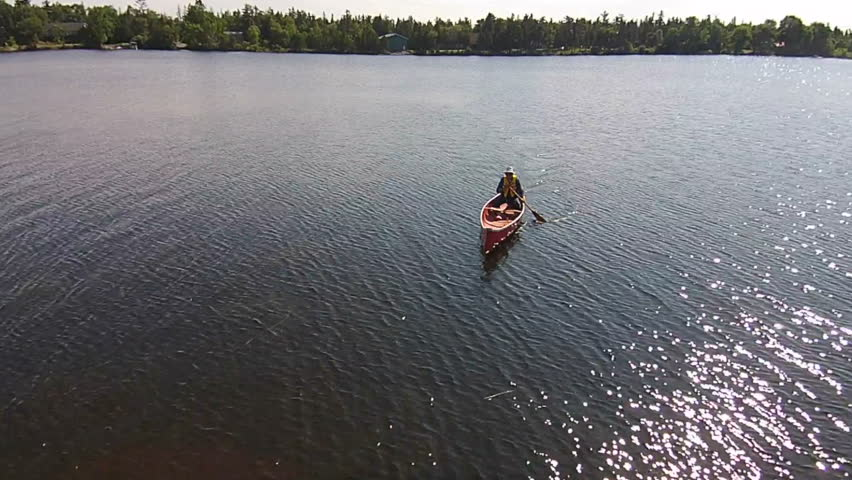 Aerial Shot Of A Man Paddling A Traditional Red Open Canoe On A Fresh Water Canadian Lake Wearing A Life Jacket And Sun Hat