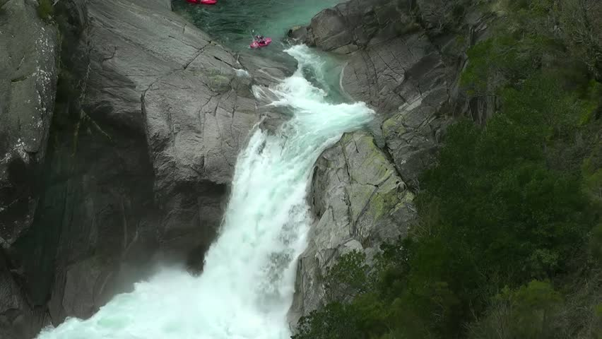 Kayaker launches himself off small fast flowing waterfall.