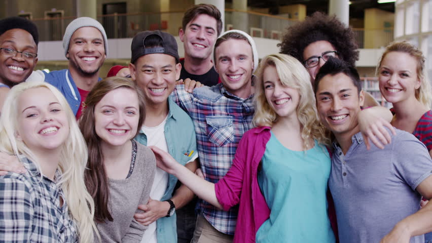 Portrait of a happy mixed ethnicity group of student friends in college library