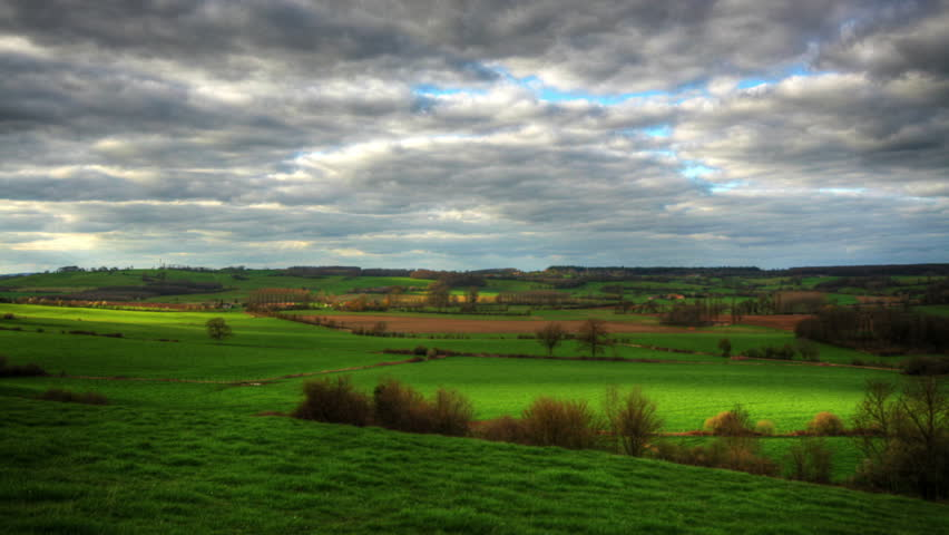 Heavy clouds passing over green hills, hd time lapse clip, high dynamic range imaging