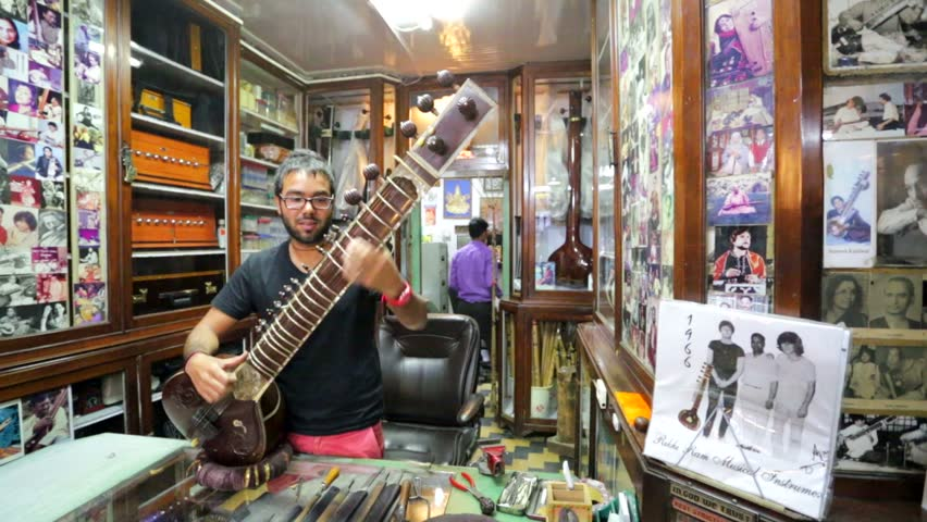 DELHI, INDIA - CIRCA MAY 2014: Indian traditional instrument craftsman adjust sitar. The Beatles visited this shop in 1966 and bought instruments, memorialized in many photographs in the shop's walls.
