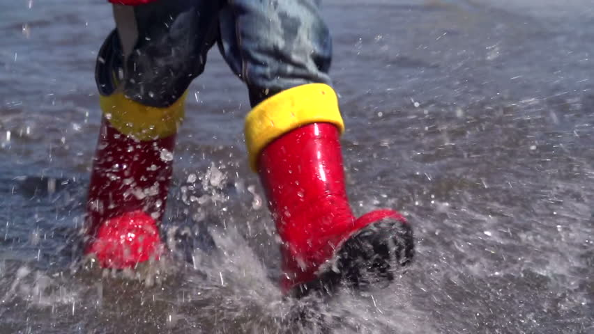 Slow motion of little boy approaching camera, going through large plash, splattering water on purpose for fun