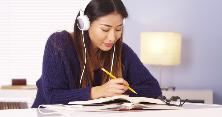 Japanese woman listening to music while doing homework - 4K stock video clip