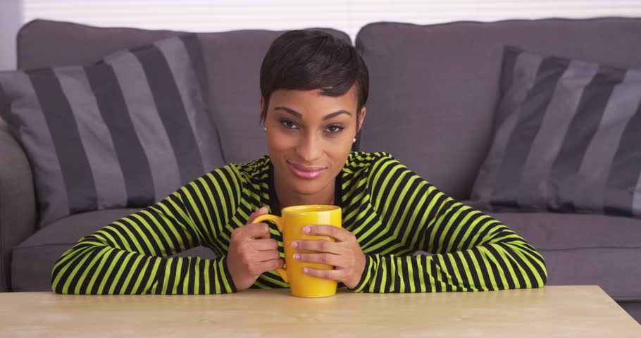 Attractive black woman sitting at coffee table with mug - 4K stock footage clip