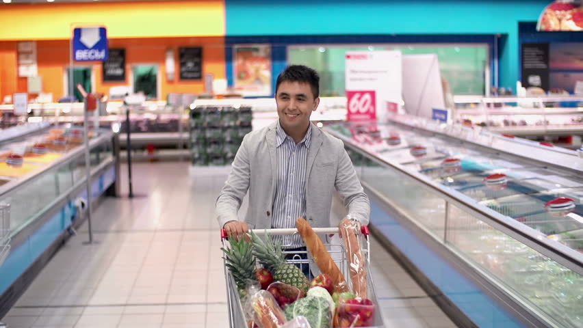 Guy with full supermarket trolley approaching camera and smiling happily