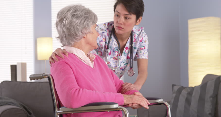 Elderly patient talking to caring Asian nurse - 4K stock footage clip