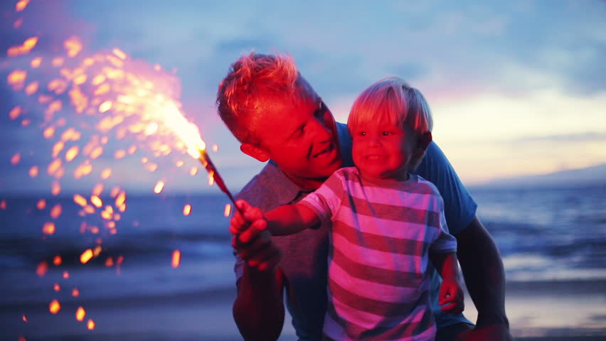 Father and son lighting sparklers on the beach at sunset - HD stock footage clip