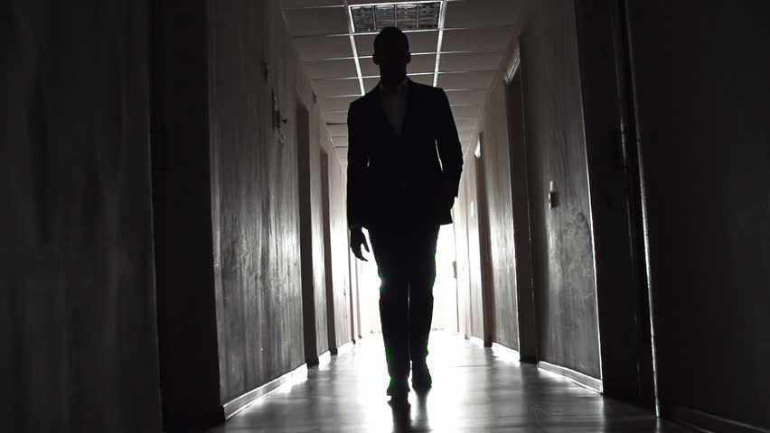 Low angle tracking shot of male outline walking along hotel corridor in slow motion, approaching camera