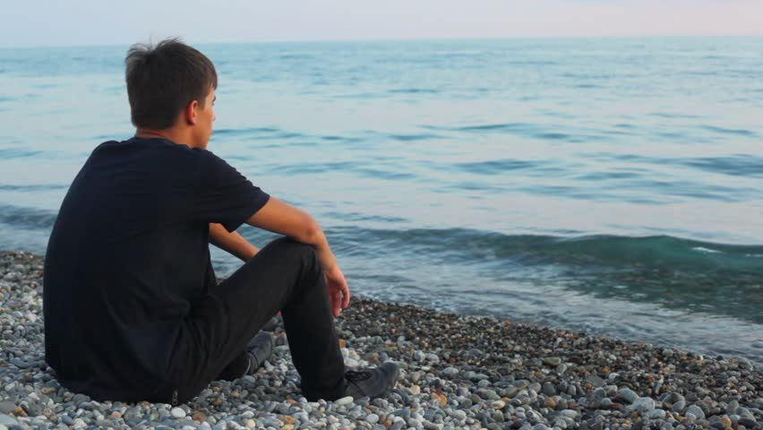 teenager sits on pebble beach and looks at sea, back view  - HD stock footage clip
