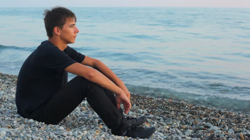 teenager sits on pebble beach and looks at sea, profile  - HD stock footage clip
