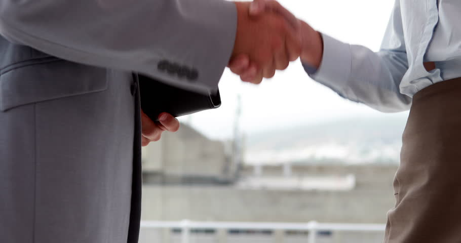 Business people shaking hands by large window in the office - 4K stock footage clip