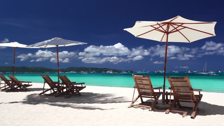 Sun umbrellas and chaise longues on caribbean beach with for Beach chaise longue