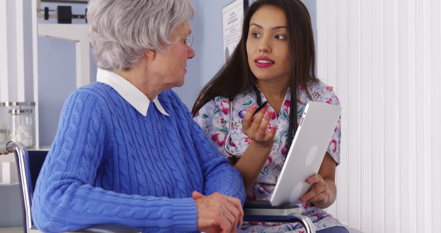 Hispanic caregiver talking with tablet with elderly patient - 4K stock footage clip
