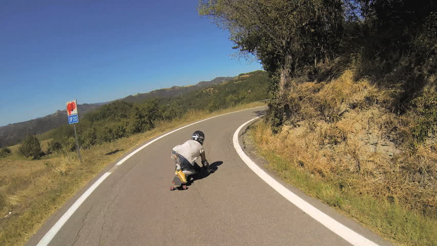 A longboarder while longboarding downhill loses his balance and falls