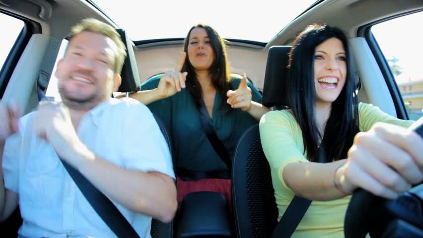 Three happy friends dancing in car