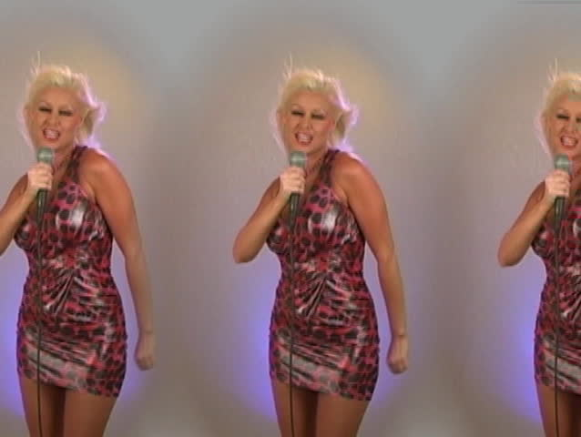 A sexy, young, busty blonde wearing a leopard-print dress holds a microphone and sings while the wind blows her luscious locks (no audio).  - SD stock video clip