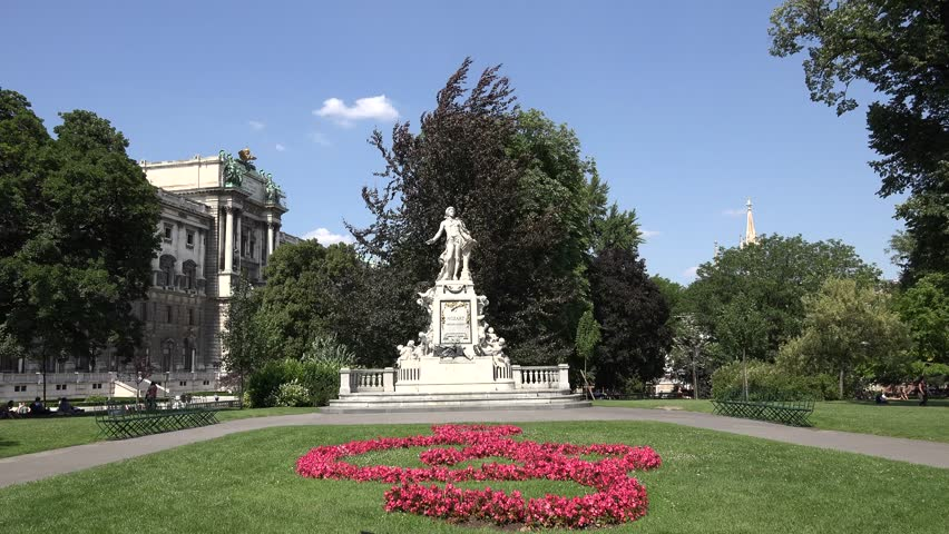 ULTRA HD 4K Beautiful musician Mozart statue in park ,garden  with flower clef in Vienna, landmark in sunny day, tourism attraction - 4K stock footage clip