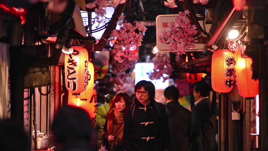 TOKYO, JAPAN - MARCH 31, 2014: People walk down a narrow restaurant-lined alleyway in Shinjuku Ward. Shinjuku is a major nightlife and entertainment district. - HD stock video clip