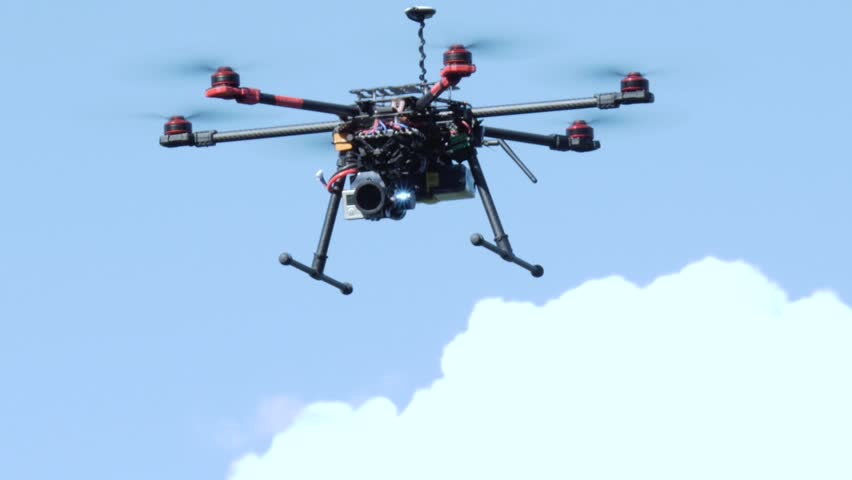 Professional drone flying in the air, in a aerial shot.
