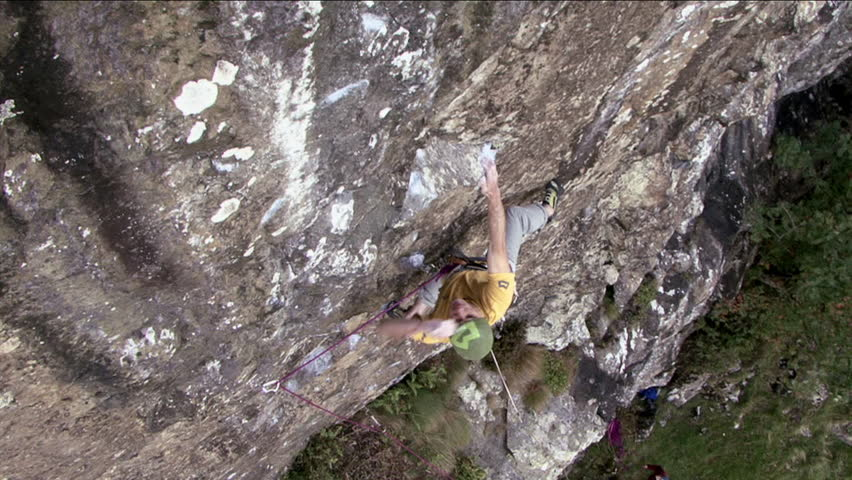 A rock climber climbs up a rock and secures his rope - HD stock video clip