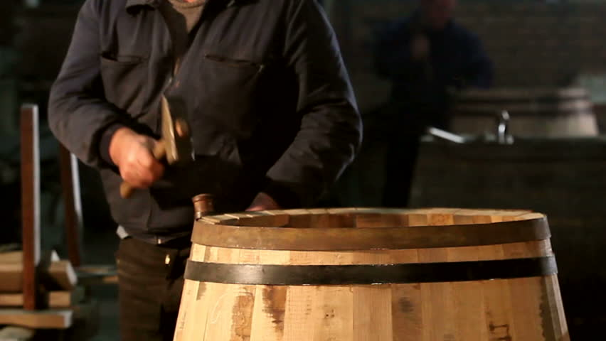 Vintage way to make barrels. Man hitting the wooden planks with a hammer