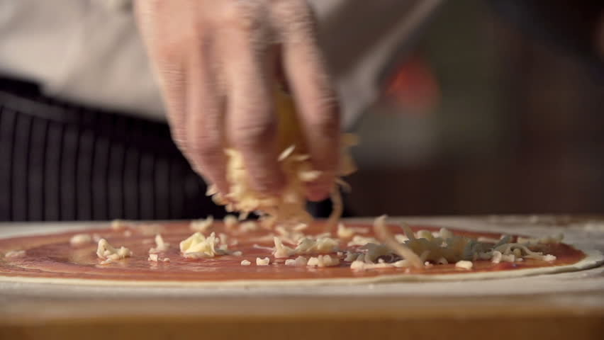 Extreme close up of unrecognizable man putting cheese topping on his pizza base