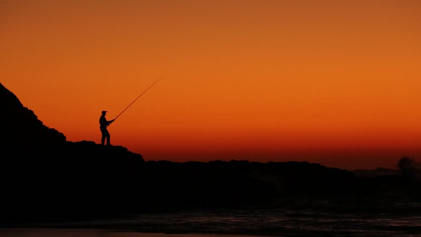 Fisherman fishing on a rock while the sun rises behind him making a beautiful silhouette. - HD stock footage clip