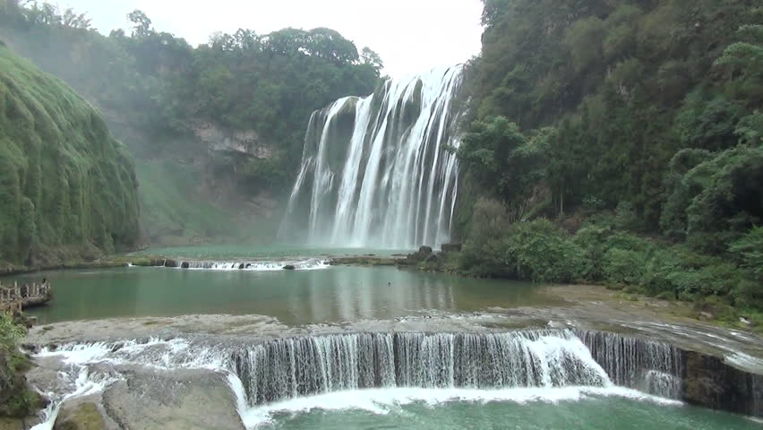 Water from a waterfall flowing into a river - HD stock video clip