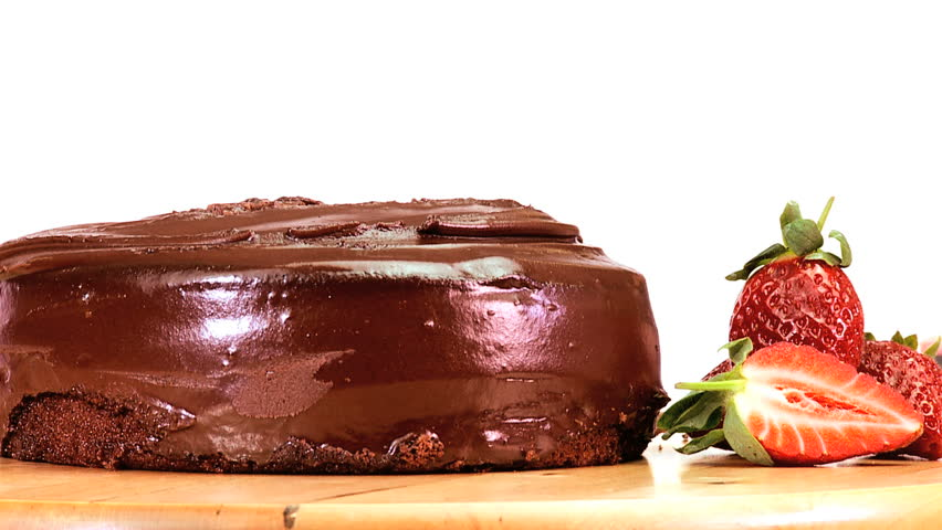 A serving of indulgent sticky chocolate cake served with fresh strawberries - HD stock video clip