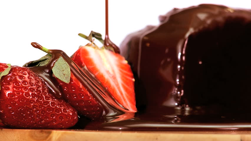 Indulgent chocolate cake & strawberries being covered in sweet sticky sauce on white background - HD stock footage clip