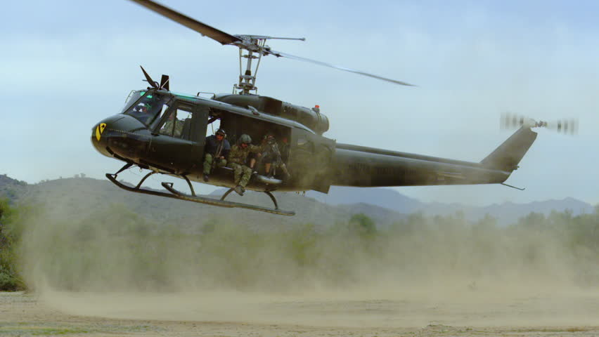 Huey helicopter lands in the desert, slow motion. - HD stock footage clip