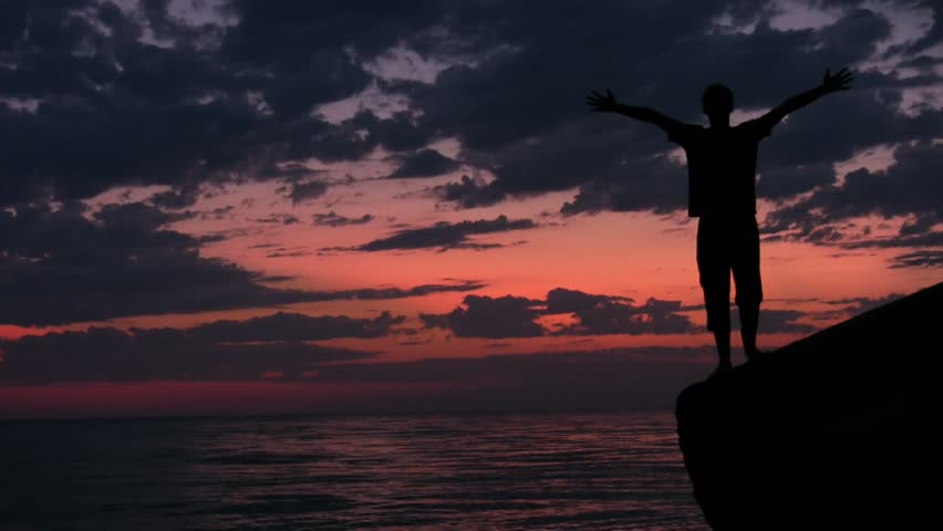 teenager stands with raised hands on rock against sunset sky and sea  - HD stock footage clip