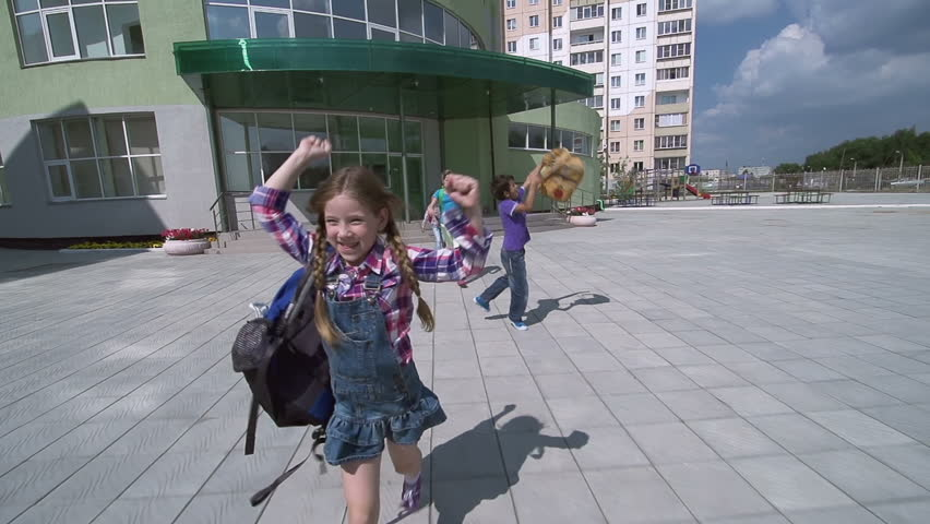 Kids approaching camera running away from school and throwing their bags in the air triumphantly