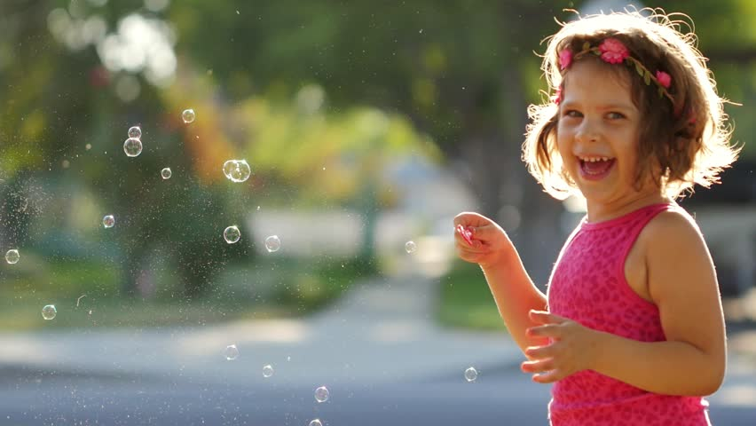 Happy girl having fun blowing soap bubbles into father's face outdoors. Slow motion. - HD stock video clip