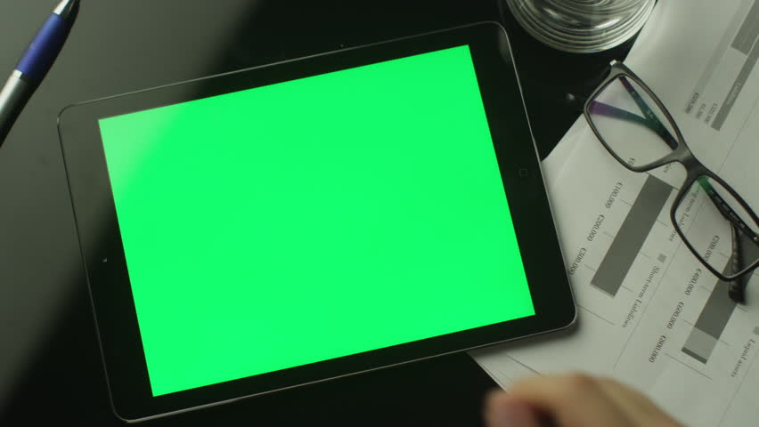 Businessman Using Tablet PC with Green Screen which Lying on the Table. Top view. Shot on RED Cinema Camera in 4K. ProResHQ codec - Great for editing, color correction.