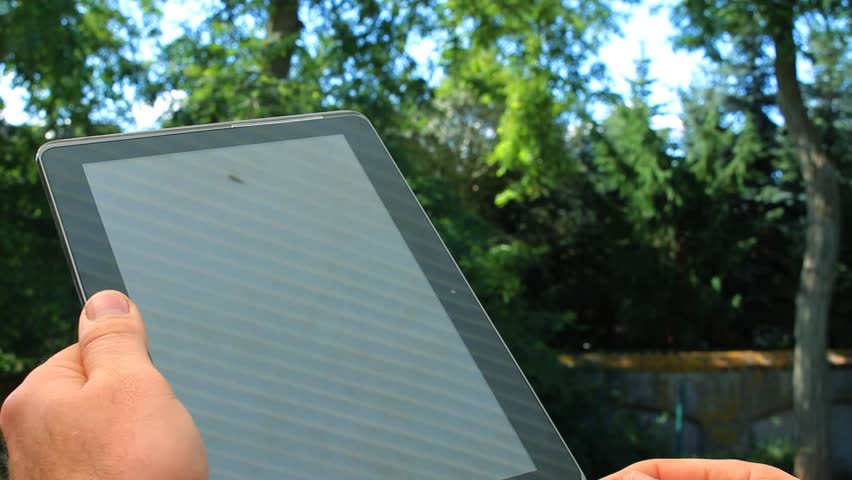 Young man using tablet pc at the park  - HD stock footage clip