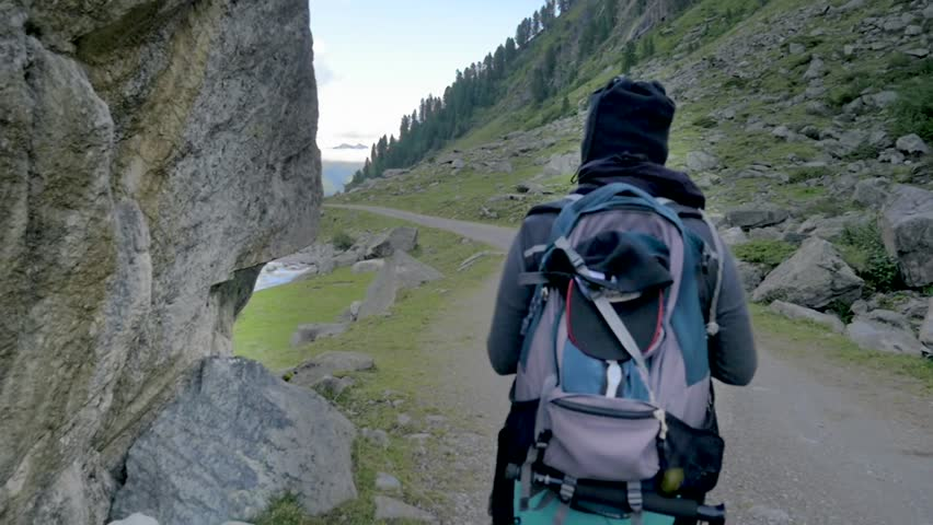 Hispanic woman hiking in Austrian valleys in slow motion with a steady cam