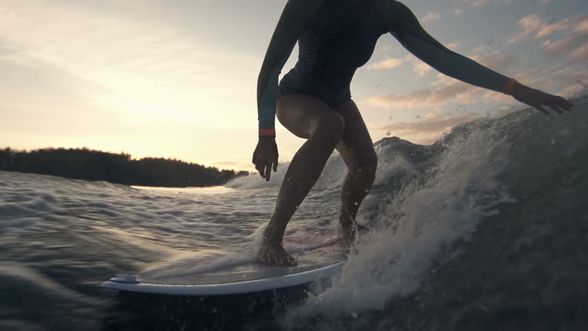 Slow motion of sportive lady surfing in the twilight