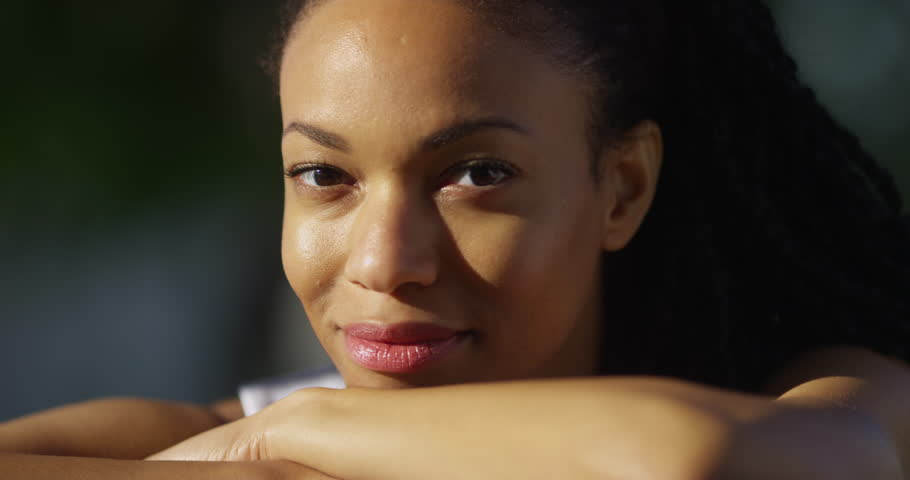 Happy black woman in a park smiling - 4K stock footage clip